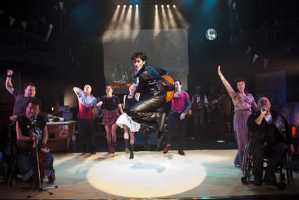 Image of man jumping in the air with serveral cast behind him on set of Reasons to be Cheerful