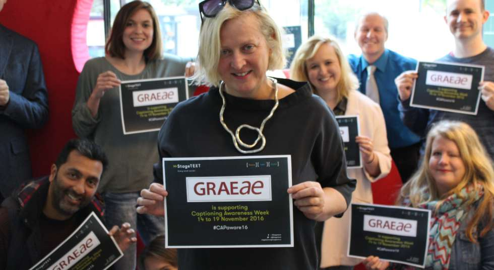 Image of some of Graeae's employees holding up signs supporting captioning awareness week