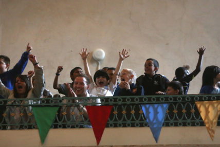 Image of Day of Games with cheering children on balcony.