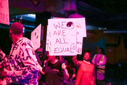 Participants holding up signs that read 'We are all equal'