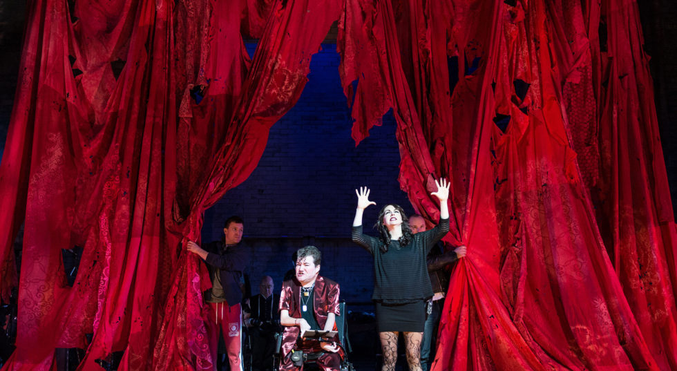 Three performers emerge from a red tattered curtain.