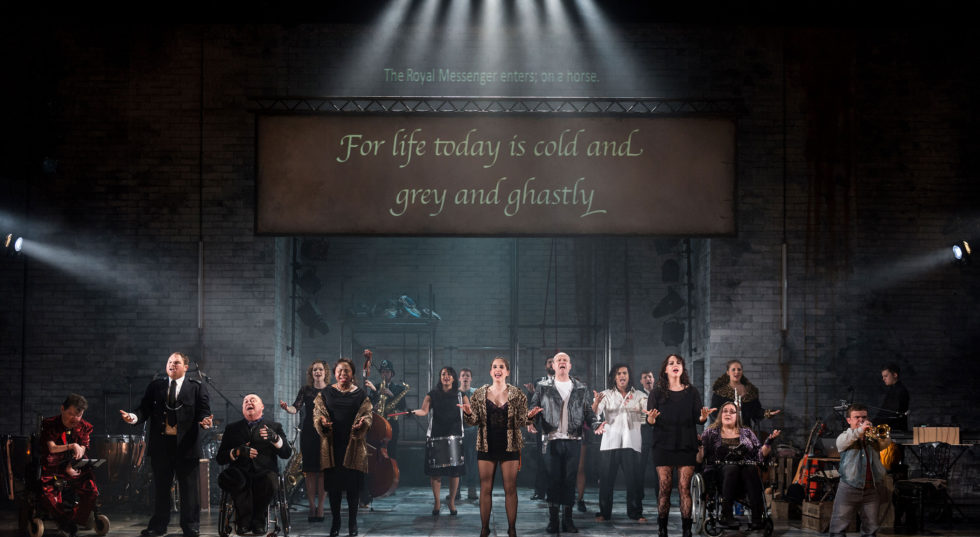 The cast assembles on stage, all singing, whilst the text behind reads 'For life today is cold and grey and ghastly'.
