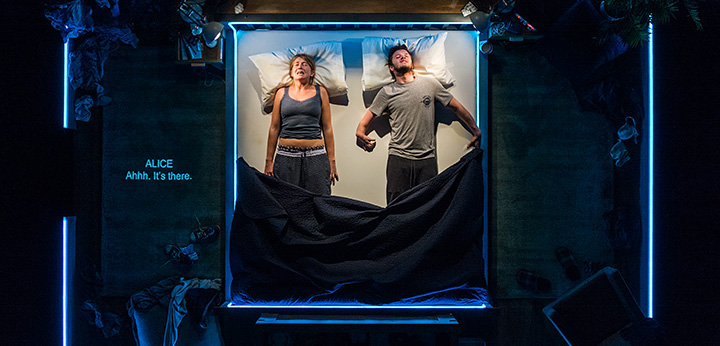 Image of Alice and Phil in bed on the set 'The Solid Life of Sugar Water