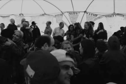 A black and white photo showing a group of people mingling and celebrating.