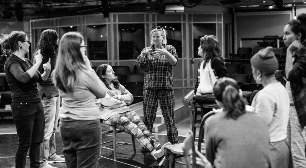 Image of Bernarda Alba cast in rehearsals circled around Jenny Sealey