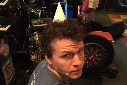 Close up of Max Runham wearing a party hat