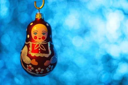 Close up of Christmas ball Matryoshka over blurred shiny background. Selective focus.
