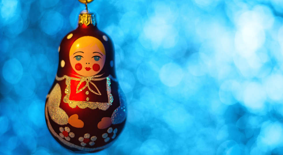 Close up of Christmas ball Matryoshka over blurred shiny background. Selective focus.