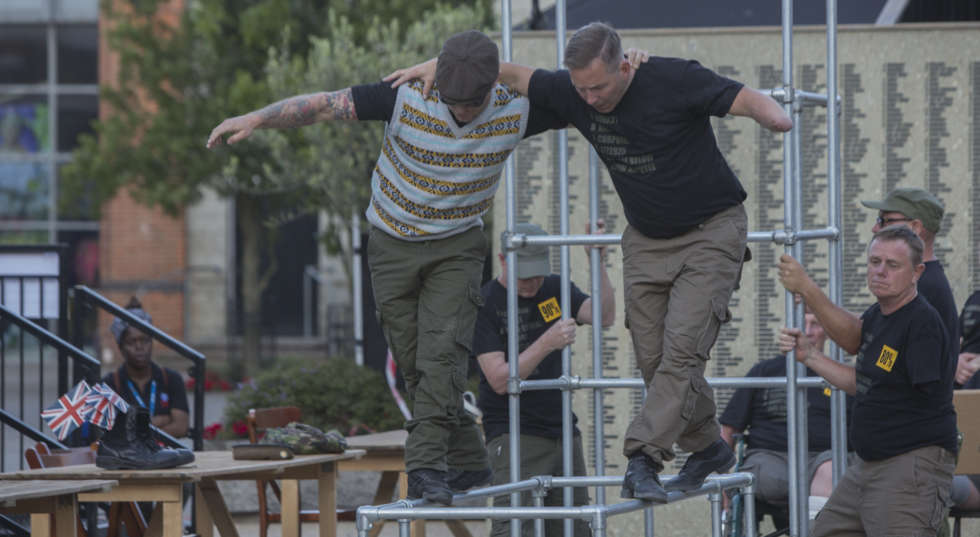 Billy Drinkwater, Kirk Bowett and Mark Brown. They walk upon a metal frame structure.