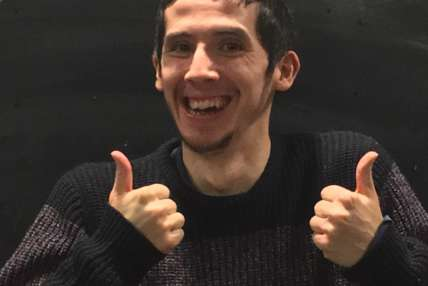 Headshot of Josh smiling with his thumbs up