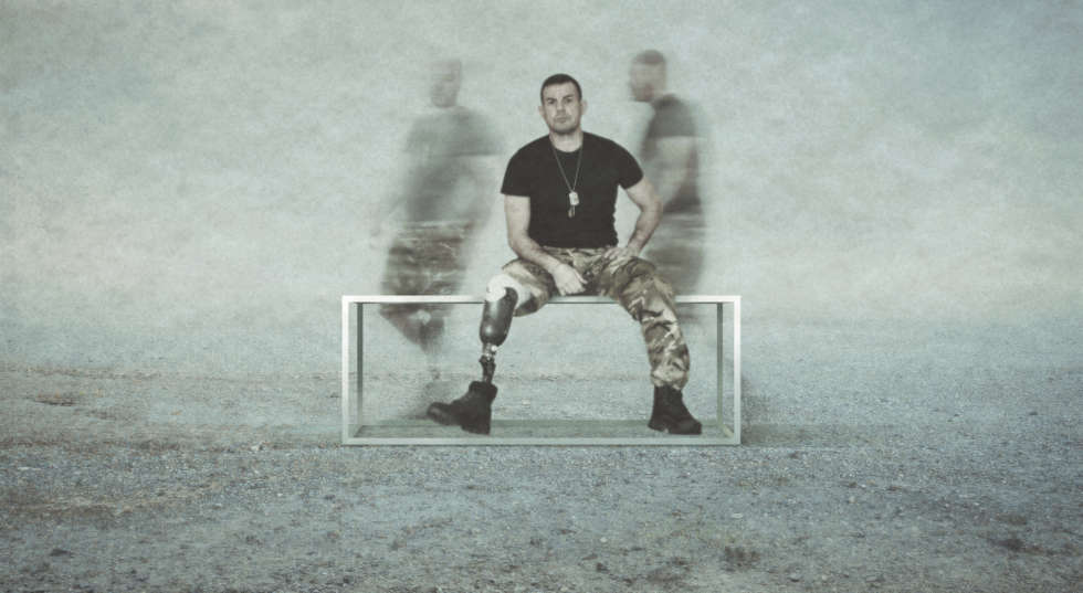 A man sits on a bench, whilst the blurry afterimages of other men flit behind him