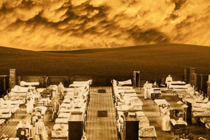 A war-time sepia image, showing rows of hospital beds with nurses standing by some of them. On the horizon can be seen rolling English hills, with a dramatic skyline behind.