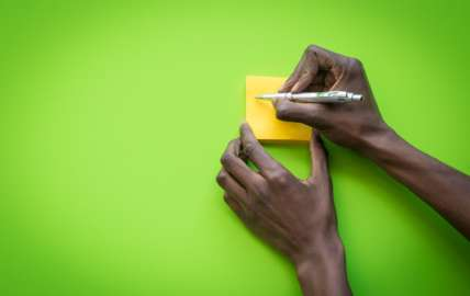An image showing a hand writing on a yellow notepad, against a lime green background
