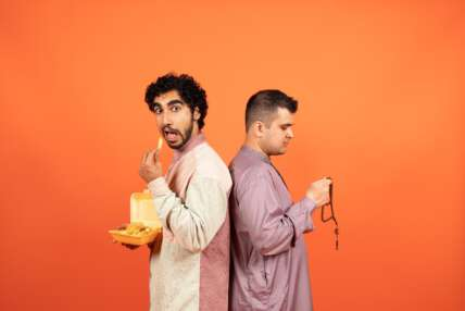 A photo showing two men standing back to back, wearing traditional Muslim dress. The man on the left eats chips, with his mouth open, looking to the camera, while the man on the right looks down, holding prayer beads. They stand against a bright orange background.