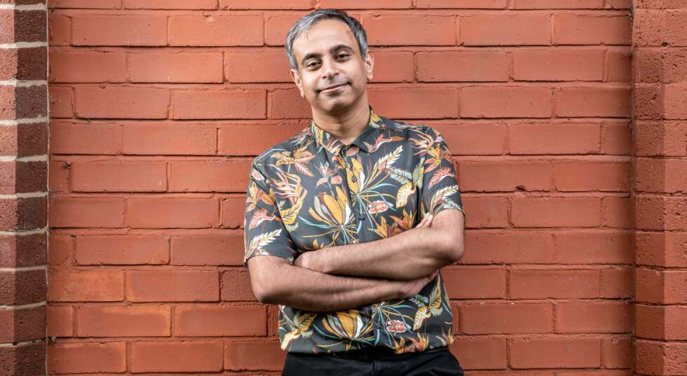 A photo showing Shahid Iqbal Khan, smiling, standing against a clay coloured brick wall. He wears a floral shirt, with his arms crossed, and smiles