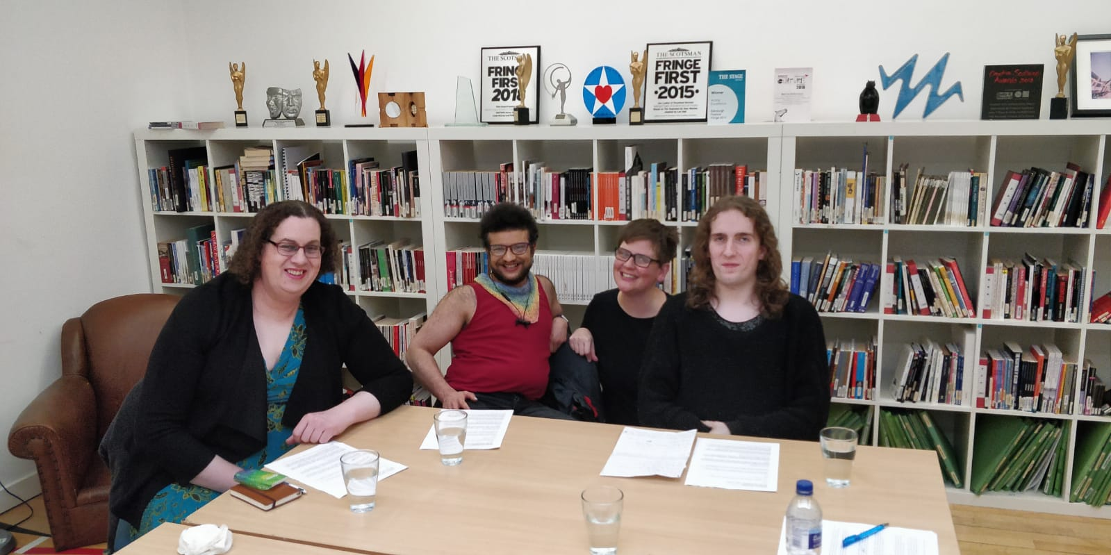 Four people sitting together round a table, smiling at the camera. Cate Lauder is a white woman with shoulder-length brown hair and glasses, wearing a blue dress and cardigan. Shafiq Ghafoor is a brown non-binary person with short, curly brown hair, a beard and glasses. They wear a red vest and rainbow scarf. Sandra Alland is a white person with short brown hair and black glasses, wearing a long-sleeved black shirt. Mattie Kennedy is a white femme with shoulder-length wavy hair, also wearing a long-sleeved black top. They sit in front of shelves of books and awards.