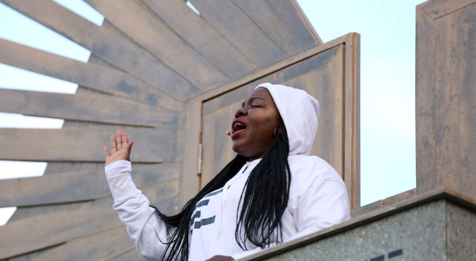 A photo of a black woman in a white hoodie, singing on top of a podium
