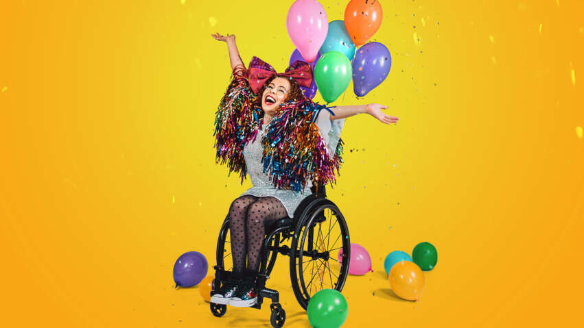 A photo of Amy Trigg, sitting in her wheelchair. She is surrounded by multi-coloured balloons, and has tinsel around her shoulders. She smiles broadly, with her arms held up. The background colour is a bright sunny yellow.