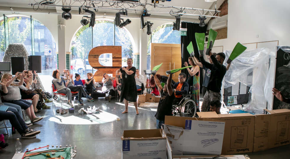 Graeae's rehearsal room with an audience watching Jenny Sealey and participants holding green flippers in the air smiling