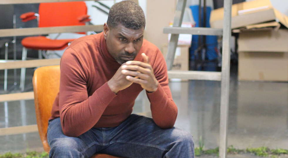 A photo showing Stanley J Browne, a black man, in rehearsals for One Under, he sits, with his arms and hands up to his face, looking to the distance pensively. He wears a rusty orange top and blue jeans.