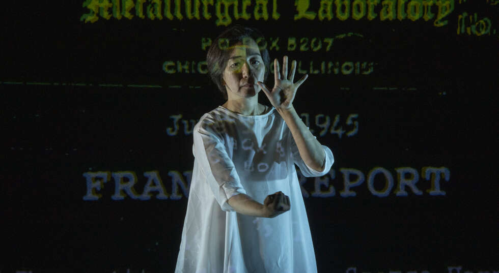A photo showing Chisato Minamimura, an East Asian woman, in performance. She wears a loose fitting white dress, and holds her left hand up and her right fist clenched. projections of words are projected behind her reading Metallurgical Laboratory and Fran Report.