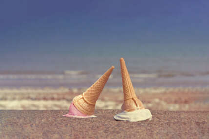 An ice cream cone dropped on a seaside pavement with the beach and sea visible in the background.