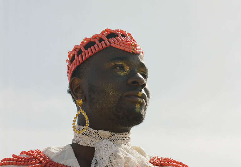 A photo showing a close up of black performer Sonny Nwachukwu, looking off to the distance. He wears a white top and white scarf, with an ornate red necklace and red headwear. He wears circular gold earrings, and gold makeup.