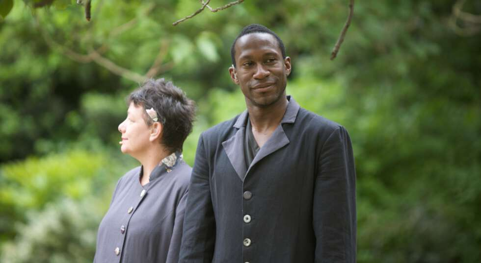 A photo showing David Ellington, a black man, during a performance of The Garden. He is visibly outside, under branches of a tree, wearing a long black button up coat. He stands next to another performer, looking off to the side.