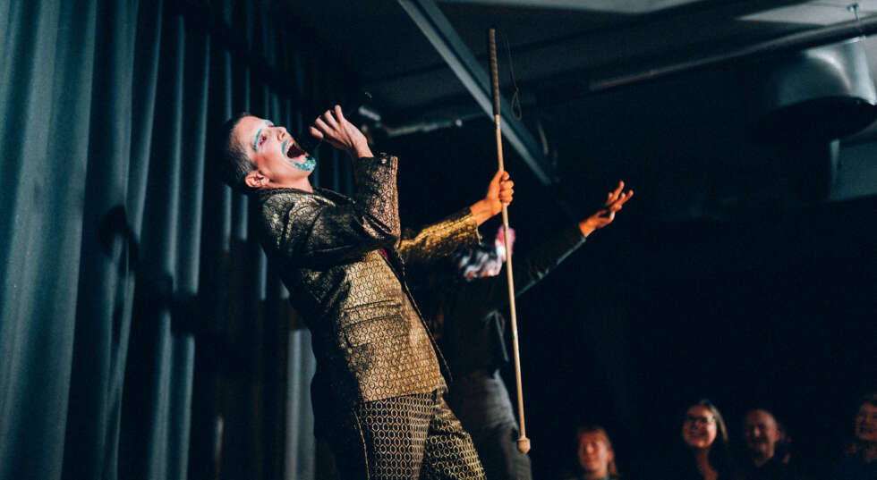 A photo showing Amelia Cavallo performing on stage. They wear a gold suit, have a goatee died blue and appear to be singing into a microphone.
